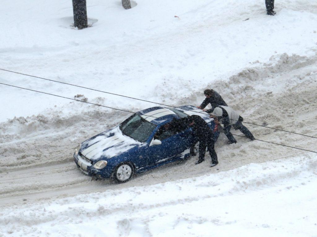 Men pushing car in snow