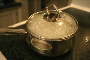 a pan and water boiing on the top of a stove